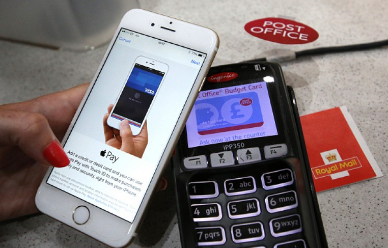 An iPhone is used to make an Apple Pay purchase at The Post Office on July 14, 2015 in London, England.